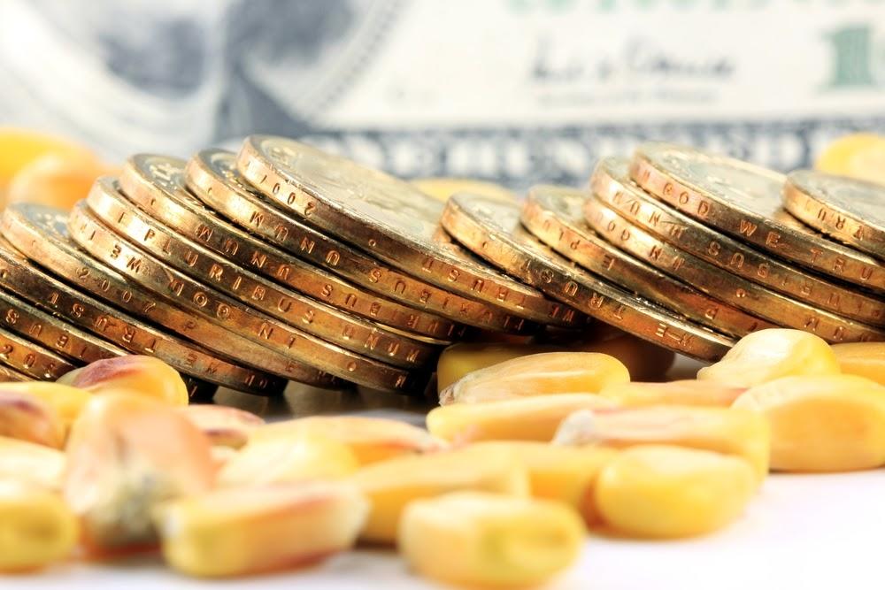 moedas ao lado de grãos de milho